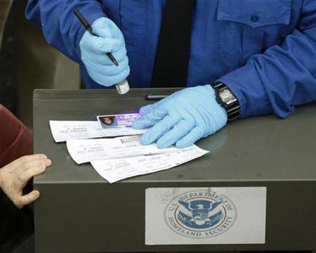 An employee of the U.S. Transportation Security Administration uses a special LED light to check the authenticity of a passenger's driver's license as he matches names on boarding passes at Washington Reagan National Airport January 4, 2010. REUTERS/Jason Reed