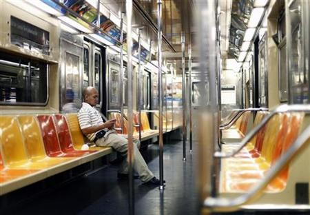 A man checks his BlackBerry phone while riding the subway in New York, August 27, 2009. REUTERS/Lucas Jackson