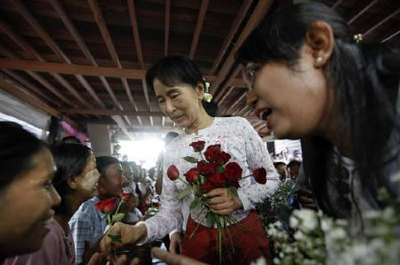 Myanmar's pro-democracy leader Aung San Suu Kyi gives flowers to patients as she visits a HIV/AIDS hospice founded by a member of her National League for Democracy (NLD) in Yangon November 17, 2010.   REUTERS/Soe Zeya Tun