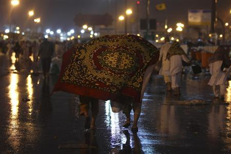 Muslim pilgrims cover themselves from rain in Mena November 17, 2010. Millions flock to Mecca in Saudi Arabia for the annual haj pilgrimage, a duty for every able-bodied Muslim who can afford it. Muslims around the world celebrate Eid al-Adha to mark the end of the haj by slaughtering sheep, goats, cows and camels to commemorate Prophet Abraham's willingness to sacrifice his son Ismail on God's command. REUTERS/Fahad Shadeed
