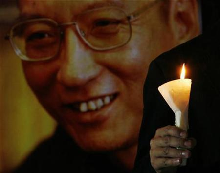 A protester holds a candle next to a portrait of jailed Chinese pro-democracy activist Liu Xiaobo during a candlelight vigil demanding the release of Liu, outside the Legislative Council in Hong Kong November 2, 2010. REUTERS/Bobby Yip