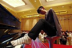 <p>Liu Wei, que não tem braços, toca o piano com os dedos do pé durante ensaio para uma televisão local. 15/11/2010 REUTERS/Petar Kujundzic/Arquivo</p>