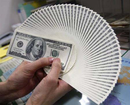 An employee of an money exchange counts U.S. dollar bills in Tokyo November 27, 2009. REUTERS/Yuriko Nakao/Files