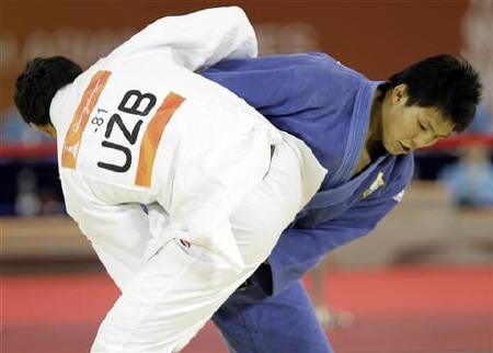 South Korea's Kim Jae Bum (in blue) competes against Uzbekistan's Shokir Muminov in the men's judo -81kg event at the 16th Asian Games in Guangzhou, November 14, 2010.   REUTERS/Jason Lee
