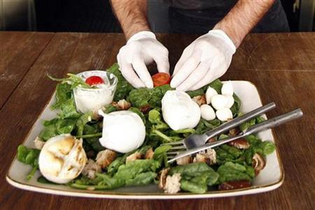 A waiter prepares a buffalo mozzarella salad in a restaurant in Rome in this October 30, 2007 photo. REUTERS/Dario Pignatelli