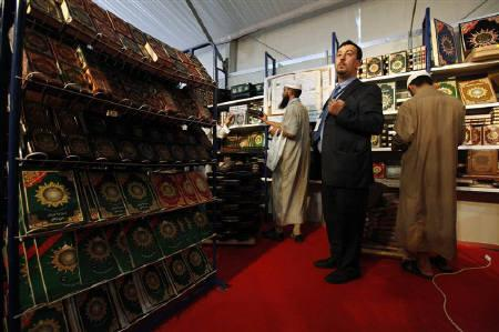 Mohamed Mouloudi (C), a publisher and importer of religious books who opposes the Salafist school of Islam, stands at his stand at the 15th International Book Fair (SILA) in Algiers October 27, 2010. REUTERS/Zohra Bensemra/Files
