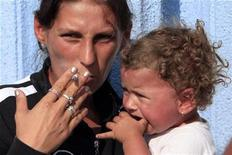 <p>A Roma mother smokes a cigarette after arriving with her family on a voluntary repatriation scheme from France in Bucharest, August 19, 2010. REUTERS/Radu Sigheti</p>