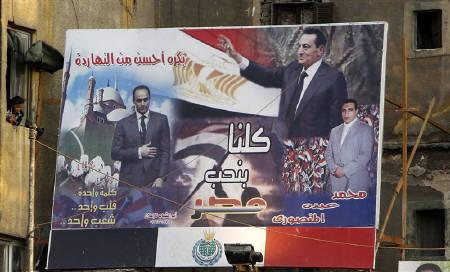 A resident stands beside an electoral banner for Egypt's ruling National Democratic Party (NDP) showing Egypt's President and head of the ruling NDP Hosni Mubarak and his son and NDP deputy head Gamal Mubarak (L) in Cairo November 22, 2010.  REUTERS/Amr Abdallah Dalsh/Files