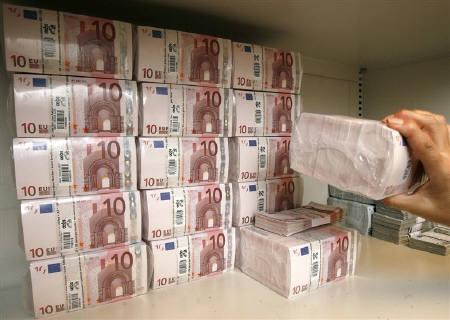 A bank clerk takes a pack of 10 Euro notes valuing 10,000 Euros (14,225 dollars) from a safe in a bank in Vienna July 21, 2009. REUTERS/Heinz-Peter Bader/Files