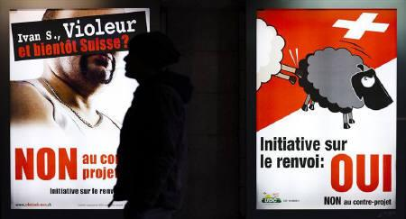 A man walks past posters of the Swiss People's Party (SVP) promoting the initiative to expel foreigners, in Lausanne, November 28, 2010. The posters read 'Ivan S., rapist and soon to be Swiss ?' and 'Yes to the initiative to expel foreigners'. REUTERS/Valentin Flauraud