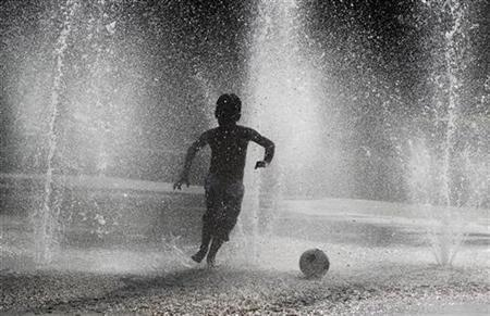 A young boy plays at a water fountain in Montreal August 31, 2010. REUTERS/Shaun Best