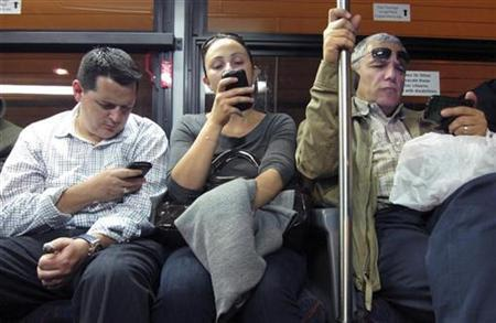 Commuters use their smartphones as they ride in a bus leaving Manhattan through the Lincoln Tunnel in New York October 8, 2010. REUTERS/Gary Hershorn