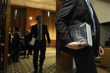 Senate staff members pick up copies of President Barack Obama's 2011 Budget as it is distributed on Capitol Hill in Washington February 1, 2010. REUTERS/Jonathan Ernst