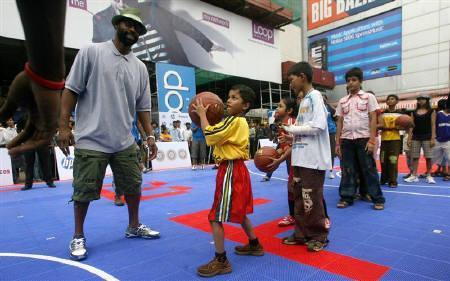 12月2日、NBAがインドでのテレビ生放送を開始することが分かった。写真左はインドで子どもたちにバスケットボールを指導するクリッパーズのバロン・デービス。昨年7月撮影(2010年 ロイター/Arko Datta)