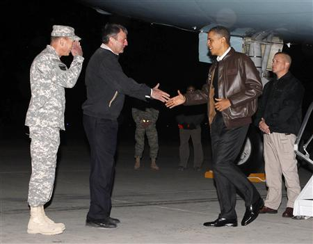 President Obama is greeted by U.S. Ambassador to Afghanistan Karl Eikenberry and Commander of U.S. forces in Afghanistan General David Petraeus as he arrives at Bagram Air Base, Afghanistan, December 3, 2010. REUTERS/Jim Young