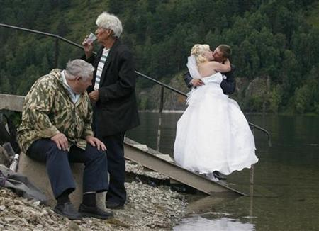 Fishermen drink and watch a newly married couple kiss on a bank of the Yenisei River in Divnogorsk, a town 38 km (24 miles) to the south of the Siberian city of Krasnoyarsk, August 13, 2010. REUTERS/Ilya Naymushin