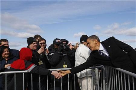 U.S. President Barack Obama reaches out over a barricade to greet people after stepping off Air Force One in Greensboro, North Carolina December 6, 2010. REUTERS/Jim Young