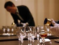 <p>A waiter is reflected in a mirror as he pours Scotch whisky from luxury brand Royal Salute into glasses at a launch ceremony for the release of the '62 Gun Salute' series in central Beijing December 6, 2010. The luxury whisky is selling at 15,000 yuan ($2,260) per bottle, with the launch consisting of a 'British Royal banquet' where 62 guests will fire 62 guns. REUTERS/David Gray</p>