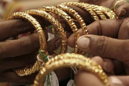 A woman holds gold bangles at a jewellery shop in Kolkata October 14, 2009. Jewellers and  investors flocked to the physical market on Wednesday after  bullion prices slipped from an all-time high around $1,430 an  ounce because of a firmer U.S. dollar, keeping premiums steady  in Asia. REUTERS/Jayanta Shaw/Files