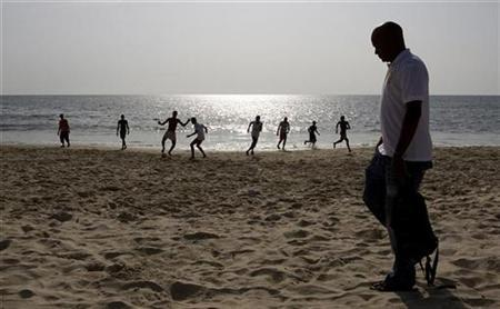 Diaspora returnee Abimbola Carrol, managing director of Visit Sierra Leone, walks past people playing football on Lumley Beach in the capital Freetown October 31, 2010. REUTERS/Simon Akam