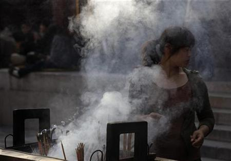 A woman turns away from the smoke while offering incense at Yonghe Lamasery in Beijing September 30, 2010. REUTERS/Petar Kujundzic