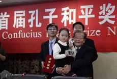 <p>A girl holds the first Confucius Peace Prize trophy after receiving it for the recipient Lien Chan, former Taiwan vice-president, as she is carried by Yang Disheng, a member of the Confucius Peace Prize jury, at the award ceremony in Beijing December 9, 2010. REUTERS/Jason Lee</p>