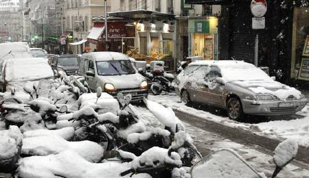 Cars drive in a snow-covered street in Paris December 8, 2010 as winter weather and sub-freezing temperatures continue in northern France. REUTERS/Benoit Tessier