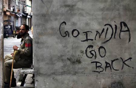 Policemen sit beside anti-India graffiti during a curfew in Srinagar August 9, 2010.  REUTERS/Reinhard Krause/Files