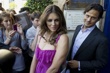 A file photo shows British model Elizabeth Hurley (L) and her husband, Indian businessman Arun Nayar leaving after the Valentino fashion house Fall/Winter 2010-2011 Haute Couture show in Paris July 7, 2010. Hurley used her Twitter account to announce that she had separated from Nayar. REUTERS/Gonzalo Fuentes/Files