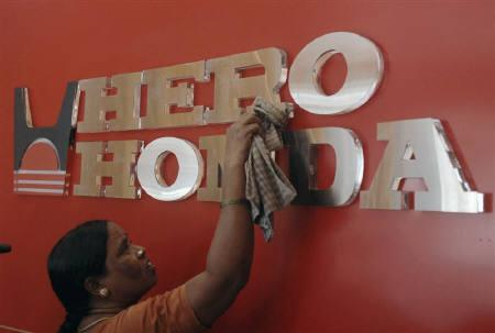 A worker cleans a Hero Honda logo inside its showroom in Hyderabad April 19, 2010.     REUTERS/Krishnendu Halder/Files