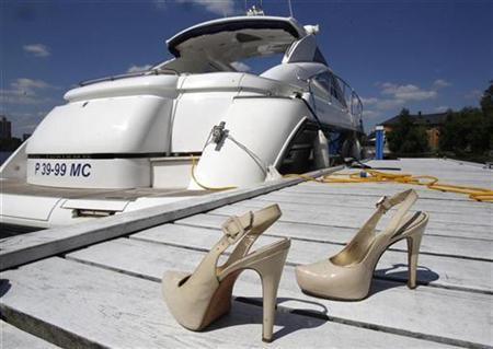 A pair of high heel shoes is placed on shore in front of a yacht during the summer contingent of the Millionaire Fair of luxury goods in Moscow, July 4, 2010. REUTERS/Sergei Karpukhin