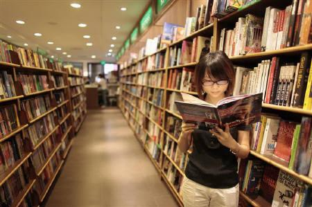 A woman reads a book at bookstore in Shanghai August 13, 2009. REUTERS/Aly Song