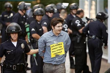 One of 21 protesters and homeowners facing foreclosure despite making payments under the Home Affordable Modification Program (HAMP) is arrested for trespassing during a protest outside the offices of Chase Bank in Los Angeles, California, December 16, 2010. REUTERS/David McNew