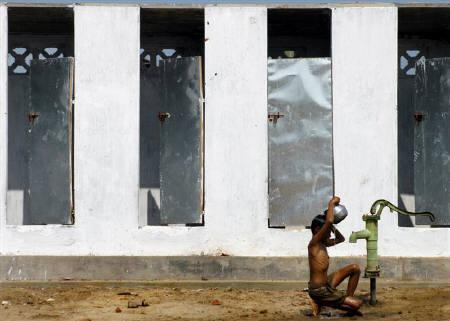 A boy takes bath outside newly built toilets in a village on the outskirts of Nagapattinam, about 325km (202 miles) from Chennai December 24, 2005. REUTERS/Jagadeesh NV/Files