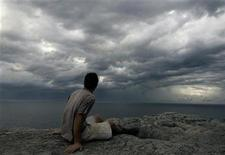 <p>A man watches seasonal autumn storm clouds gather over the sea ahead of steady rain off the coast of Sydney March 8, 2007. REUTERS/Will Burgess</p>