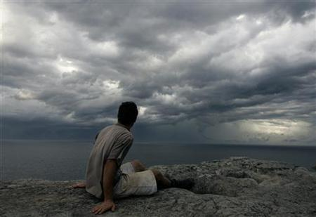 A man watches seasonal autumn storm clouds gather over the sea ahead of steady rain off the coast of Sydney March 8, 2007. REUTERS/Will Burgess