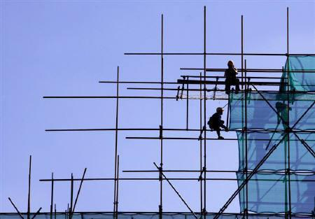 Construction workers erect scaffolding on a new residential building in central Beijing, September 10, 2010. REUTERS/David Gray/Files