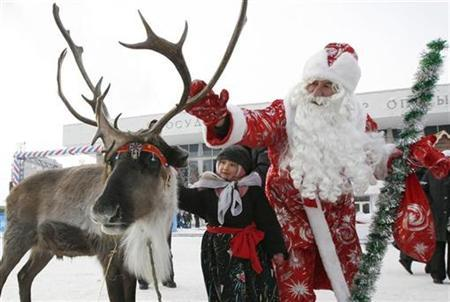 A man dressed as Father Frost, the equivalent of Santa Claus, and a child touch an Evenki reindeer at the Christmas food fair in central Krasnoyarsk, December 18, 2010. REUTERS/Ilya Naymushin