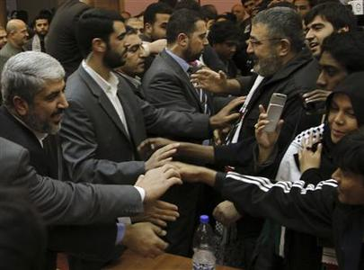 Hamas leader Khaled Meshaal (L) greets members of the ''Asia 1'' convoy after a meeting in Damascus December 22, 2010. REUTERS/Khaled al-Hariri