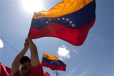 Supporters of Venezuela's President Hugo Chavez hold the national flag as they greet the official caravan on the road to the venue of the Africa-South America Summit on Margarita island September 26, 2009. REUTERS/Carlos Garcia Rawlins