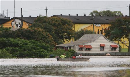 Two men boat along a flooded street in Bundaberg, Queensland, Australia December 29, 2010. REUTERS/Jono Searle/Pool