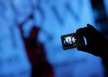 A visitor takes pictures of an adult film actress during the Eros Show in the Bulgarian capital Sofia April 2, 2008.  REUTERS/Stoyan Nenov