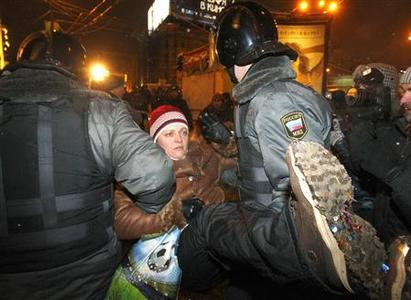 Riot police officers detain a woman during a protest rally to defend article 31 of the Russian constitution in Moscow December 31, 2010. REUTERS/Mikhail Voskresensky