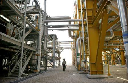 A worker walks amid facilities at phases 2-3 of the South Pars gas field, are illuminated at night in Assaluyeh on Iran's Persian Gulf coast May 27, 2006.REUTERS/Morteza Nikoubazl
