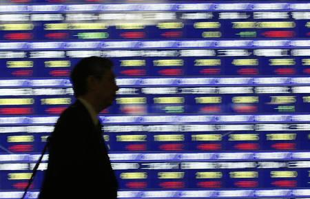A man walks past a stock quotation board outside a brokerage in Tokyo January 29, 2008. Asian stocks advanced on Tuesday and oil hovered near a 27-month high, supported by U.S. data suggesting a recovery in the world's biggest economy was gathering momentum. REUTERS/Issei Kato/Files