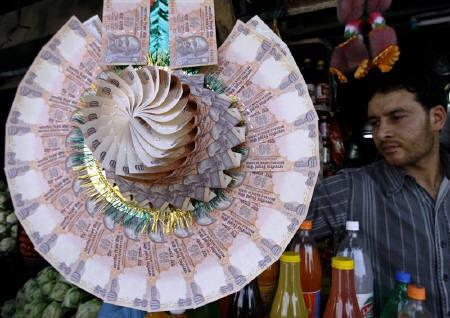 A Kashmiri shopkeeper displays a garland made of Indian currency notes at a market in Srinagar May 20, 2008. Weakened British bank note printer De La Rue will not be awarded new contracts to supply currency paper to the Reserve Bank of India (RBI) in the near future, a source close to the development told Reuters. REUTERS/Fayaz Kabli/Files
