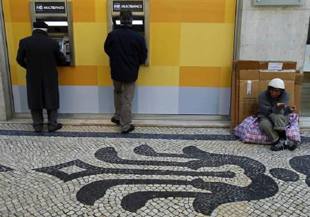 A man begs for money beside people using automated teller machines in downtown Lisbon December 16, 2010. REUTERS/Jose Manuel Ribeiro