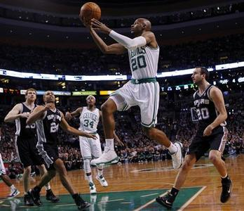 Boston Celtics guard Ray Allen (C) drives to the basket past San Antonio Spurs guard Manu Ginobili (R) in the first quarter of their NBA game in Boston, Massachusetts January 5, 2011. REUTERS/Brian Snyder