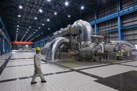 A power station staff worker walks past a steam-turbine power generator in the Waigaoqiao No. 3 power station in Shanghai March 8, 2010. REUTERS/Aly Song