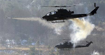 A South Korean army's AH-1S helicopter fires a missile during a live fire drill in Yangpyeong, east of Seoul, January 6, 2011. REUTERS/Han Sang-gyun/Yonhap
